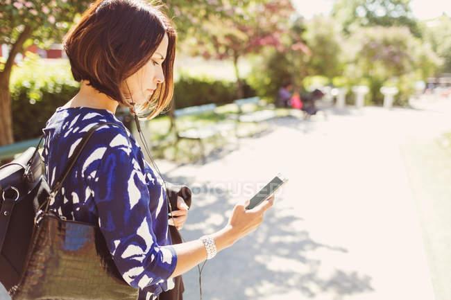 Seitenansicht der Geschäftsfrau mit Smartphone auf Fußweg an sonnigen Tag — Stockfoto