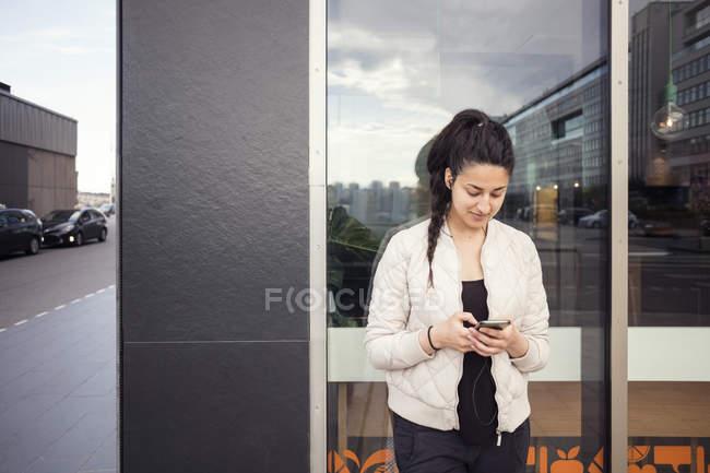Giovane donna che utilizza smartphone contro finestra — Foto stock