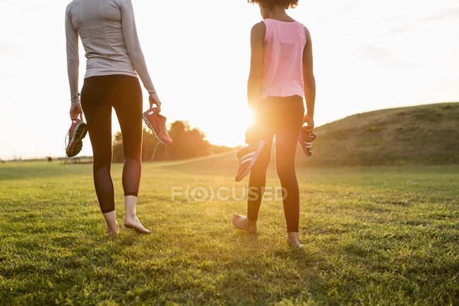 Bassa sezione di madre e figlia che tengono scarpe sportive mentre camminano sull'erba al parco durante il tramonto — Foto stock
