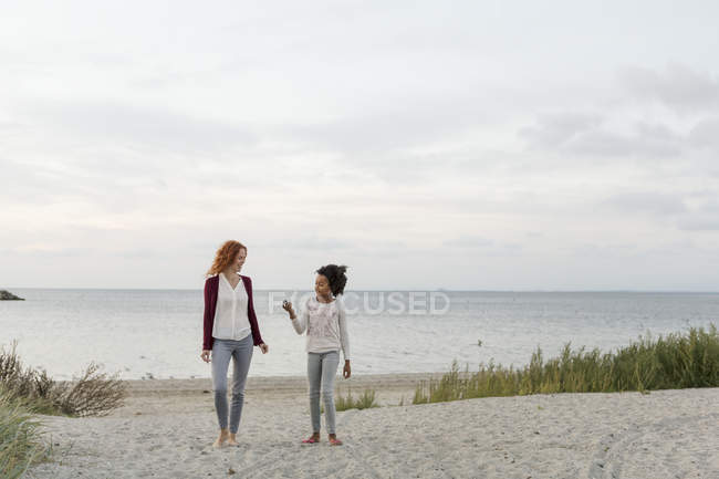 Mother and daughter walking on sand at beach against sky during sunset — Stock Photo