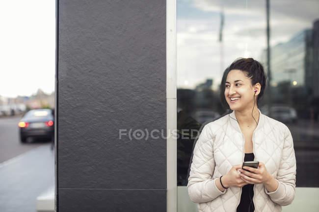 Donna felice che usando smartphone contro la finestra — Foto stock