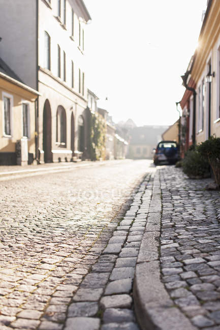 View of paved road and pavement between buildings — Stock Photo