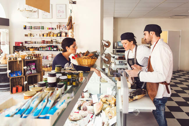 Side view of woman buying grocery from owners at store — Stock Photo