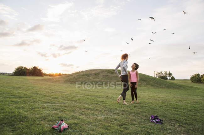 Mãe e filha de pé juntos na grama no parque contra o céu — Fotografia de Stock