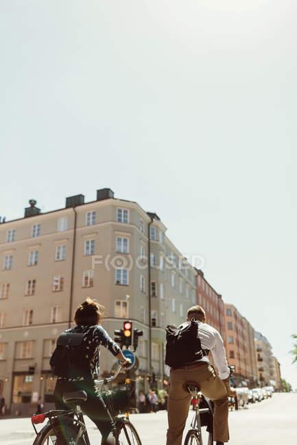 Низкий угол обзора деловых коллег, катающихся на велосипедах по улице города против ясного неба — стоковое фото