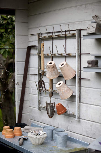 Garden tools and flower pots hanging on wooden wall — Stock Photo