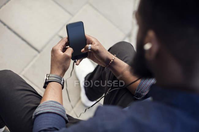 Vista de ángulo alto del hombre navegando por la red en el teléfono móvil - foto de stock