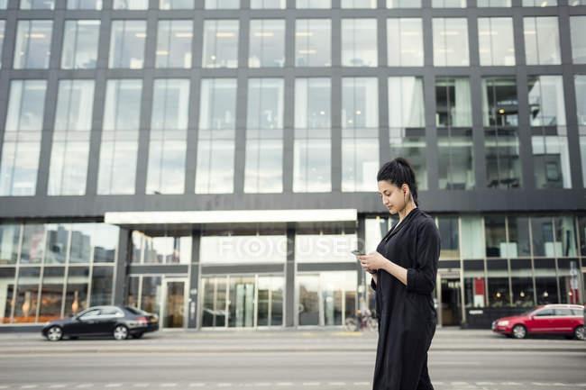 Giovane donna che utilizza il telefono cellulare contro edificio in città — Foto stock