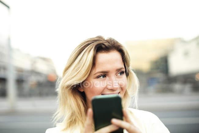 Счастливый молодая женщина, с помощью мобильного телефона в городе против ясного неба — стоковое фото