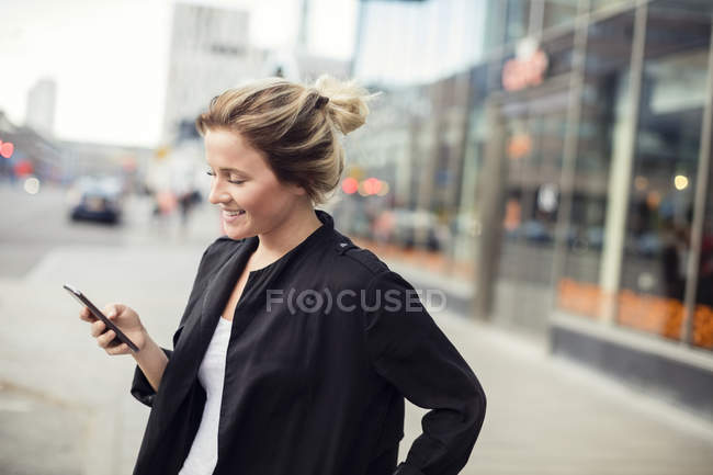 Happy woman holding mobile phone while standing in city — Stock Photo