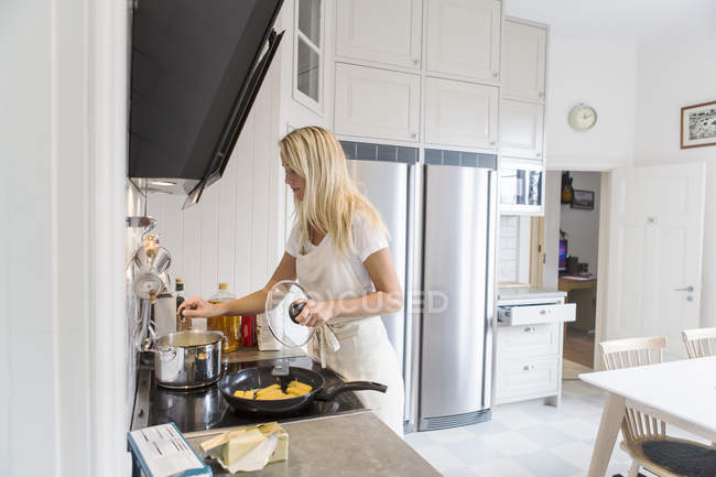 Teenage girl cooking food in kitchen at home — Stock Photo