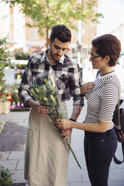 Female customer buying flowers from male owner on sidewalk — Stock Photo