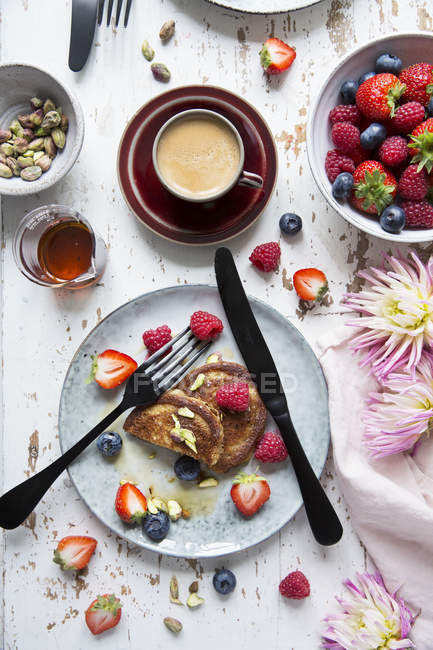 Top view of fritters with berries in ceramic plate on wooden table — Stock Photo
