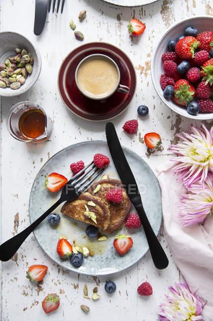 Вид сверху блинчики с ягодами в керамической пластиной на деревянный стол — стоковое фото