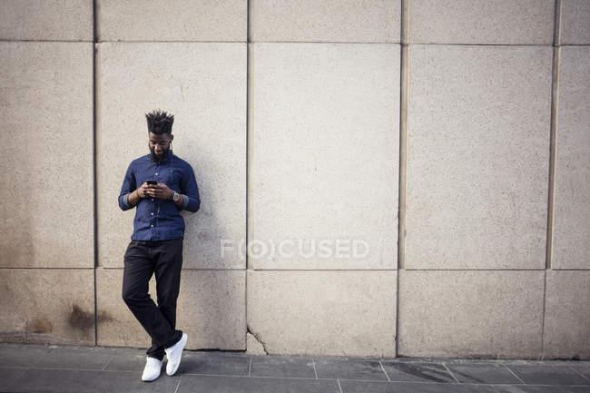 Uomo che ascolta musica dal cellulare contro muro — Foto stock