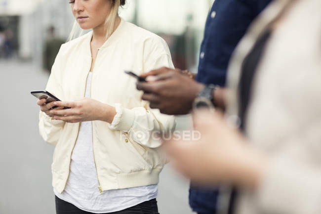 Midsection of young friends using smart phones in city — Stock Photo