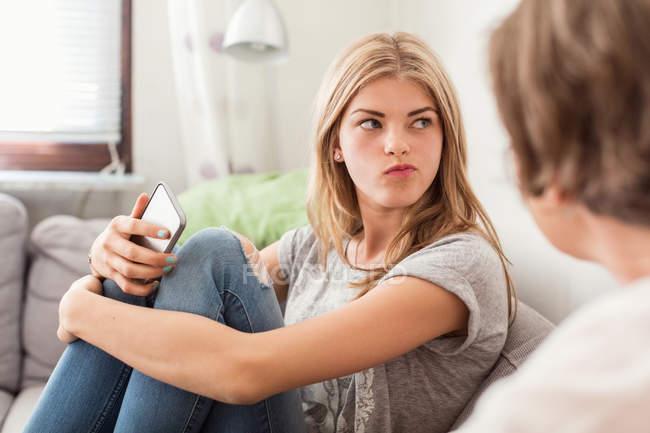 Adolescente menina fazendo rostos enquanto sentado com a mãe no sofá em casa — Fotografia de Stock