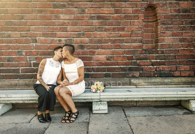 Newlywed lesbian couple kissing while sitting on bench against brick wall — Stock Photo