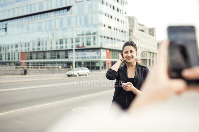 Обрезанное изображение женщины, фотографирование подруге в городе — стоковое фото