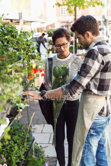 Woman buying flowers from male owner on sidewalk — Stock Photo