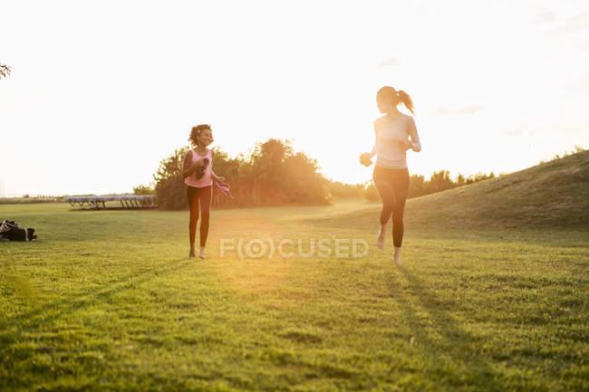Menina feliz correndo com a mãe na grama no parque contra o céu durante o pôr do sol — Fotografia de Stock