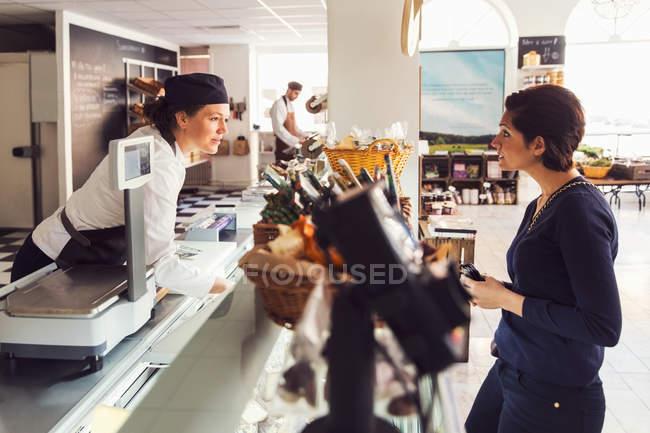 Vista laterale della donna che parla con la commessa al banco al negozio di alimentari — Foto stock