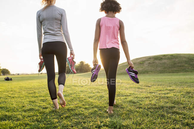 Rear view of mother and daughter holding sports shoes while walking on grass at park during sunset — Stock Photo