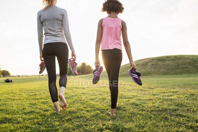 Vista traseira de mãe e filha segurando sapatas dos esportes enquanto caminhava na grama no parque durante pôr do sol — Fotografia de Stock