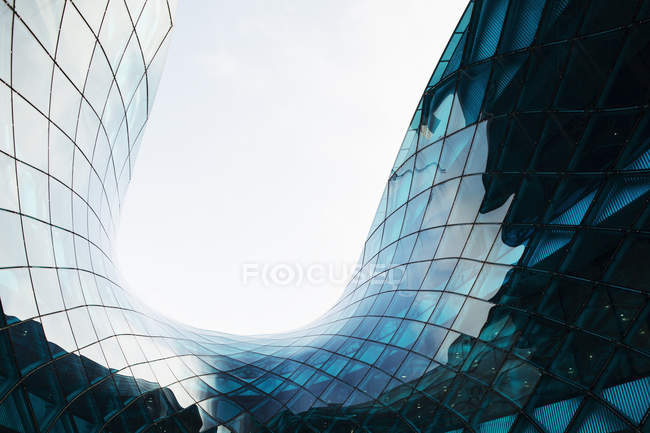 Vista inferiore di vetro moderno grattacielo contro il cielo — Foto stock