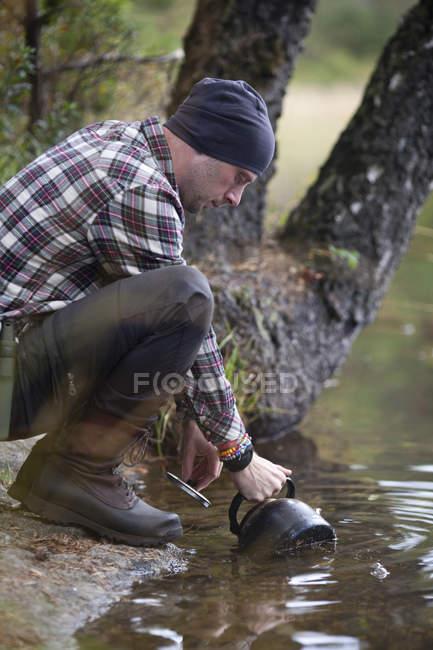 Vista laterale dell'uomo riempiendo d'acqua nel bollitore dal lago campeggio — Foto stock