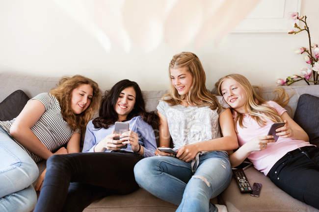 Щасливі дівчаток-підлітків за допомогою смарт-телефону, лежачи на дивані у вітальні — стокове фото