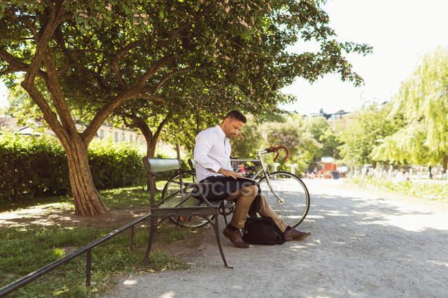 Empresário usando laptop enquanto sentado no banco no parque — Fotografia de Stock