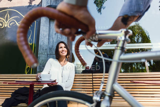 Cropped image of businessman with bicycle talking to colleague at sidewalk cafe — Stock Photo