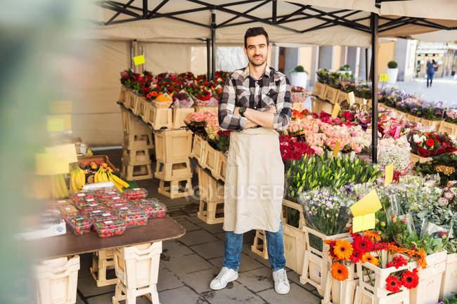 Повна довжина портрет впевненого чоловічого власника стоячи зброї перетнув в квітковий магазин — стокове фото