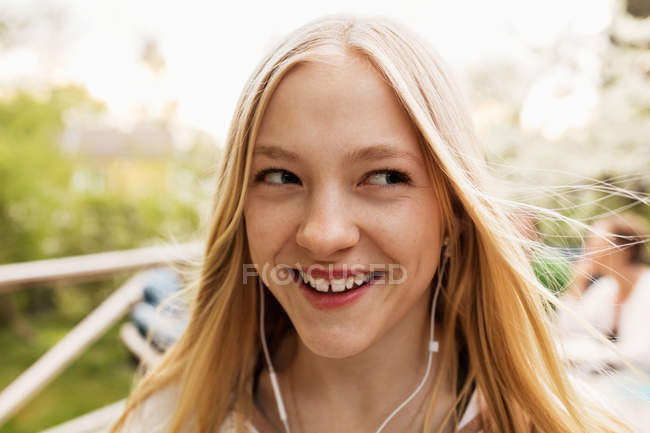 Счастливая девочка-подросток слушает музыку во дворе — стоковое фото
