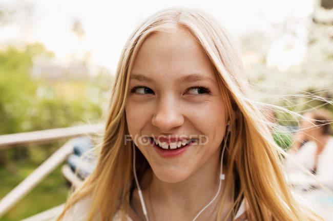 Adolescente feliz que escuta a música na jarda — Fotografia de Stock