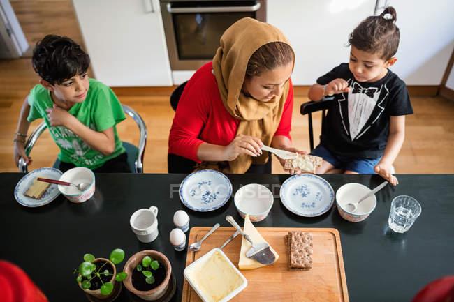 Высокий угол зрения матери применения сливочного масла на крекер для сыновей за обеденным столом — стоковое фото