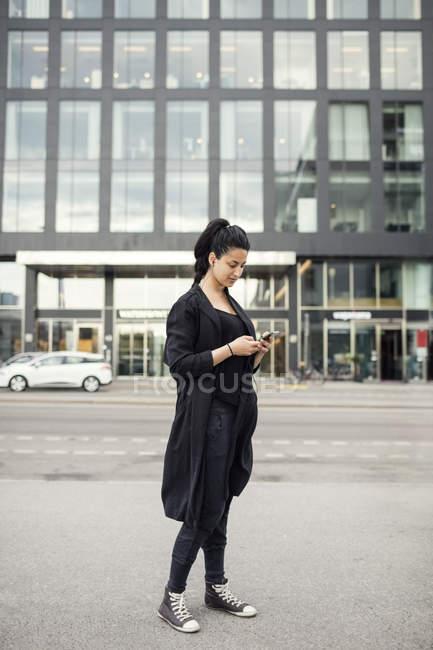 Donna che utilizza il telefono cellulare contro edificio in città — Foto stock