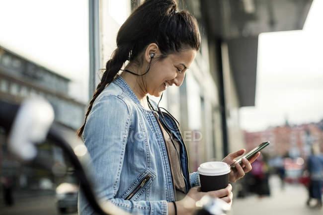 Вид сбоку женщина держит смартфон и чашка кофе в городе — стоковое фото