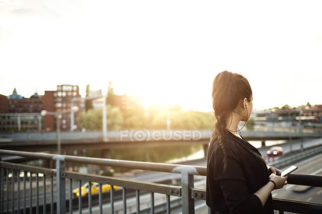 Vista laterale della donna con cellulare in piedi sul ponte contro il cielo — Foto stock