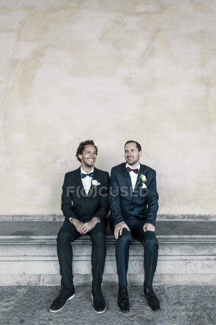 Happy newlywed gay couple sitting on bench against wall — Stock Photo