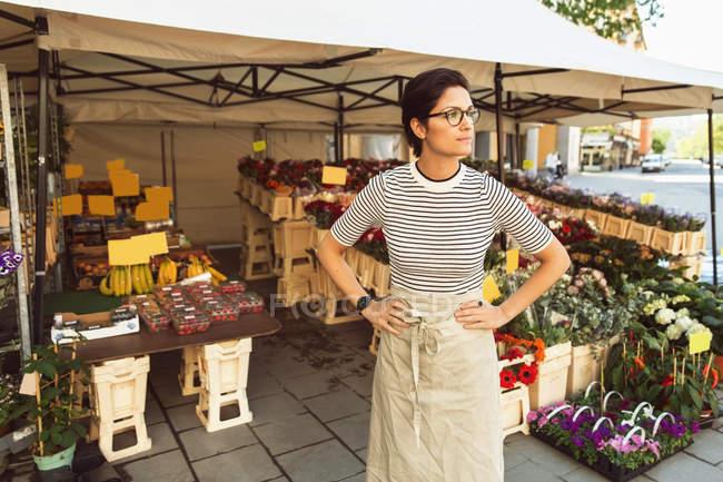 Premuroso proprietario femminile in piedi con le mani sulla moda fuori negozio di fiori — Foto stock