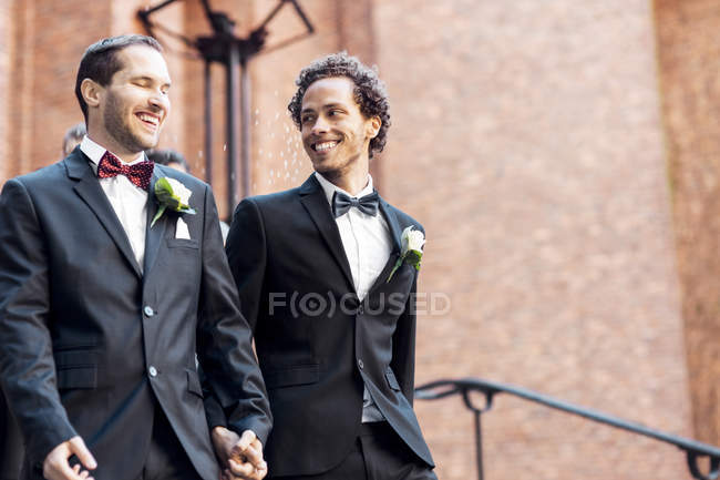 Low angle view of happy gay couple walking while holding hands — Stock Photo
