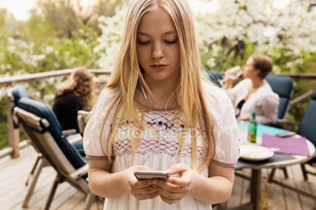 Ragazza adolescente utilizzando smart phone in cortile con la famiglia seduta in background — Foto stock