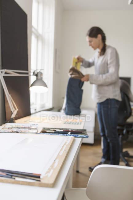 Beleuchtete Schreibtischlampe auf Tisch mit dem Künstler stehen im Hintergrund — Stockfoto