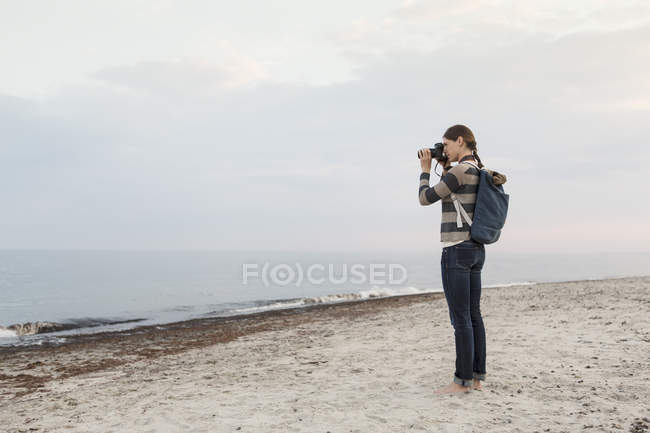 Full length of woman carrying backpack photographing sea against sky — Stock Photo
