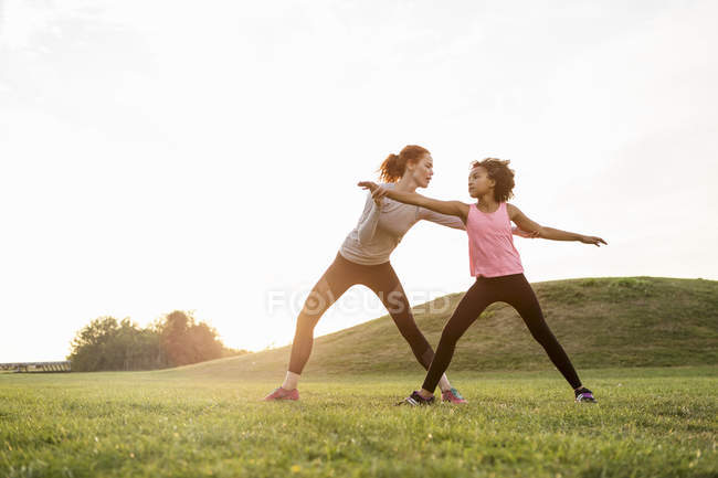Mother assisting daughter practicing exercise on grass at park against sky — Stock Photo