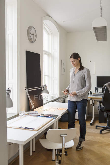 Full length of artist standing by table in creative office — Stock Photo