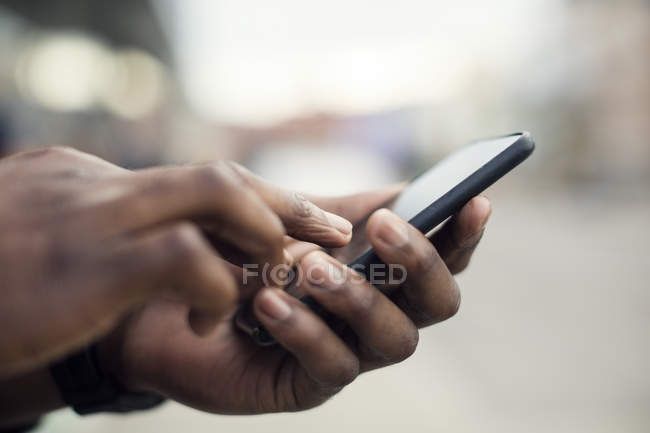 Side view of male hands using smartphone — Stock Photo