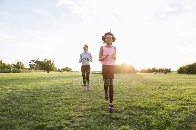 Girl and woman jogging on grass at park against sky during sunset — Stock Photo